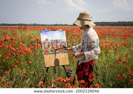 Mature woman artist paints a picture on a poppy field. Hand holds a brush and makes a smear of paint, portrait at work in half size