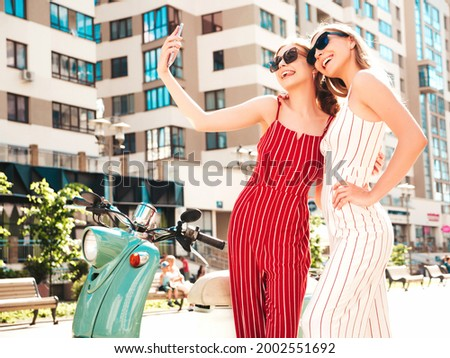 Two young beautiful smiling hipster female in trendy overalls.Sexy carefree women driving retro motorbike in the street.Positive models having fun, riding classic Italian scooter.Taking selfie photos