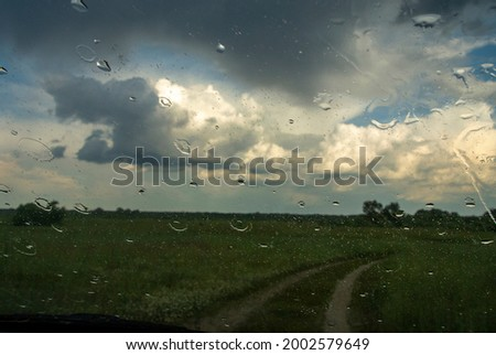 raindrops on the glass of the car. view of the meadow, road and clouds in the sky Royalty-Free Stock Photo #2002579649