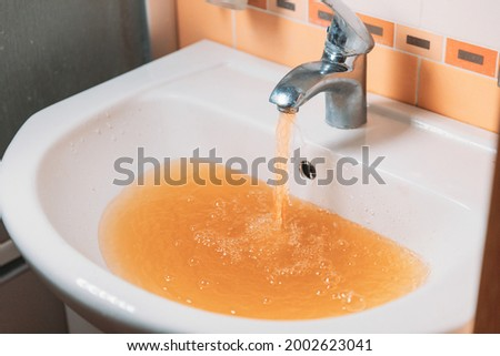 Rusty Water Pours From Tap. Water Pollution. Global Environment. Royalty-Free Stock Photo #2002623041