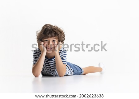 Lying on floor. Little smiling cute Caucasian preschool boy in casual clothing propping his head in hands isolated on white studio background. Concept of emotions, facial expressions. Royalty-Free Stock Photo #2002623638