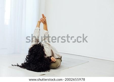 Beautiful woman brunette engaged in yoga asana gymnastics flexibility