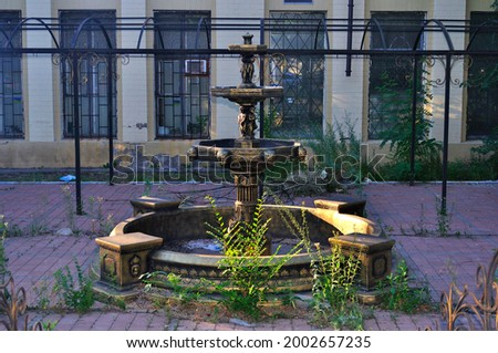 Abandoned fountain without water, apocalypse fountain view, apocalyptic fountain, ancient fountain in the park Royalty-Free Stock Photo #2002657235