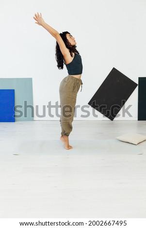 Beautiful brunette woman engaged in yoga asana gymnastics flexibility