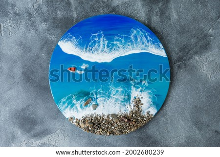 Resin art round painting. Epoxy art composition with blue ocean waves, boat and stones beach. Flat lay, top view