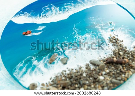 Resin art round painting. Epoxy art composition with blue ocean waves, boat and stone beach.