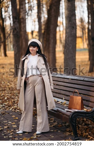 Picture of beautiful woman goes for a walk to the autumn park
