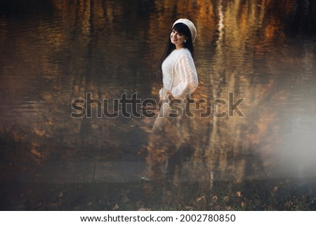 Picture of attractive woman goes for a walk near the river, rejoices and enjoys of her llife