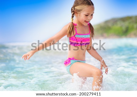 happy girl on a  tropical beach ocean has a fun with splash