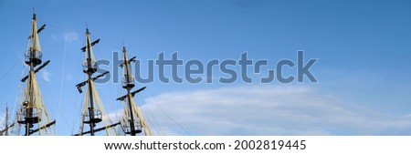 The masts of the old ship on the background of the blue sky. The concept of travel Copy space and banner Royalty-Free Stock Photo #2002819445