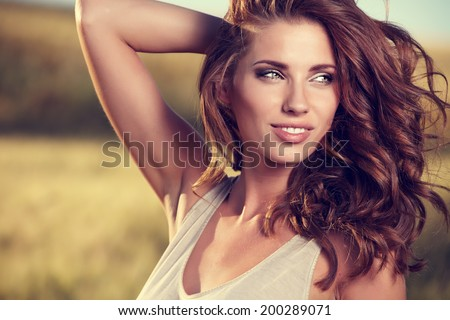 Portrait of a  woman on golden cereal field in summer  #200289071