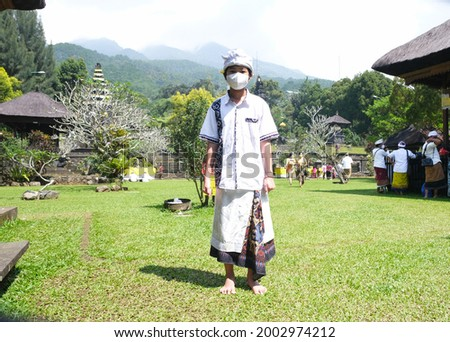 Asian boy in traditional Balinese cloth take picture at Pura Parahyangan Agung Jagatkarta Gunung Salak, a Balinese style Hinduism temple in Bogor, West Java, Indonesia.