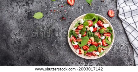 Diet menu. Healthy salad of fresh strawberry, spinach leaves, nuts and feta cheese, balsamic vinegar. Vegan food. Long banner format. top view.