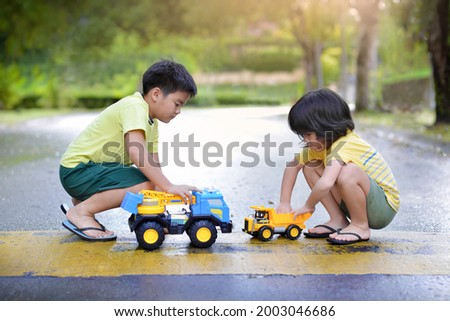 Asian children playing with trucks on the road.Elementary students with construction mobile truck.Boys imaginative automobile play.Vehicle and transportation toys.
