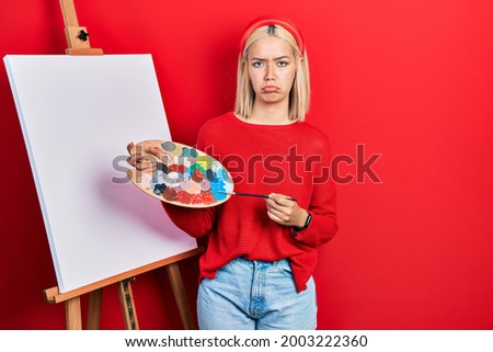 Beautiful blonde woman standing drawing with palette by painter easel stand depressed and worry for distress, crying angry and afraid. sad expression.