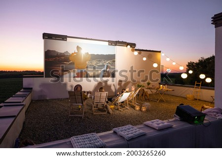 Small group of people watching movie on the rooftop terrace at sunset. Open air cinema concept. Romantic leisure and entertainment on the roof of a country house Royalty-Free Stock Photo #2003265260
