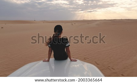 Young traveller woman sitting on the car in desert. Travel concept. Royalty-Free Stock Photo #2003365664