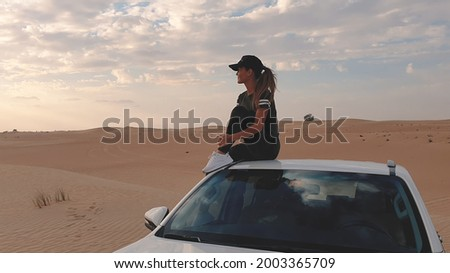 Young traveller woman sitting on the car in desert. Travel concept. Royalty-Free Stock Photo #2003365709
