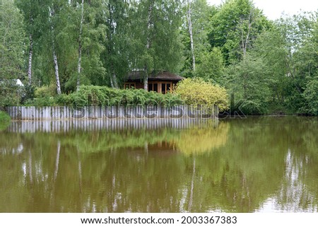 Summer wooden Lake house inside forest . High quality photo Royalty-Free Stock Photo #2003367383