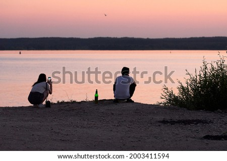 A guy and a girl are sitting on the shore of a lake at sunset. There is a bottle of beer next to the guy. A girl takes pictures of the landscape on her phone.
