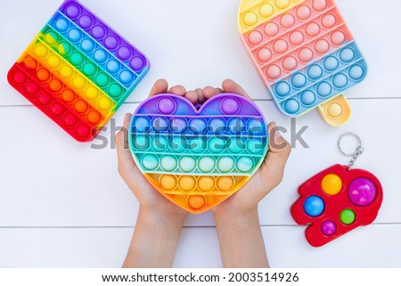 """A child with a colorful game """"Pop it"""". Anti-stress. Close-up of children's hands playing with the popular pop It fidget toy. Autism. Royalty-Free Stock Photo #2003514926"""