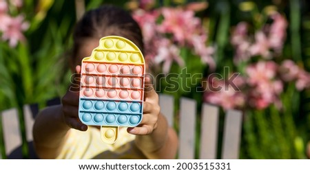 """A child with a colorful game """"Pop it"""". Anti-stress. Close-up of children's hands with the popular pop It fidget toy. Autism. Royalty-Free Stock Photo #2003515331"""