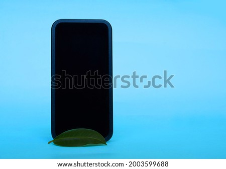 A smartphone with an empty black screen and a green ficus leaf. Blue background. Space for text.