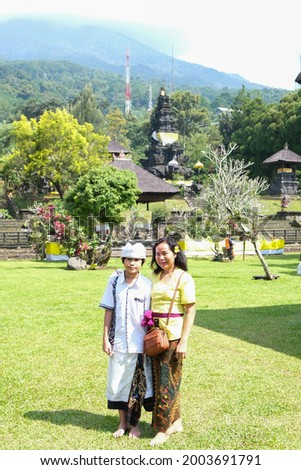 Asian mother and son in traditional Balinese cloth take picture at Pura Parahyangan Agung Jagatkarta Gunung Salak, a Balinese style Hinduism temple in Bogor, West Java, Indonesia.