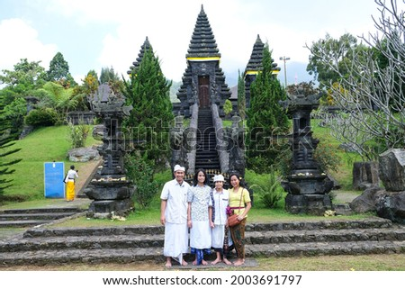 Asian family in traditional Balinese cloth take picture at the gateway to Pura Parahyangan Agung Jagatkarta Gunung Salak, a Balinese style Hinduism temple in Bogor, West Java, Indonesia.