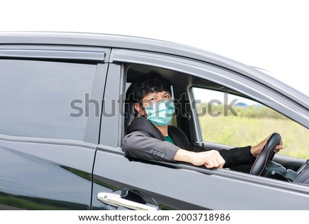 A man wearing a work suit drives a sedan to work in the city. wearing a medical mask to prevent infection during the coronavirus epidemic The driver of the sedan wears a mask for Covid-19. Royalty-Free Stock Photo #2003718986