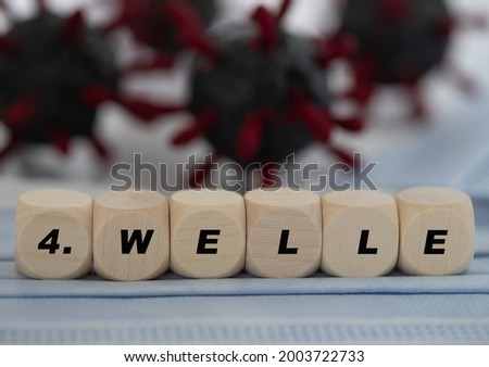 wooden cubes with the german word for 4th wave, concept for the corona spreading of delta virus variant, virus model in the background