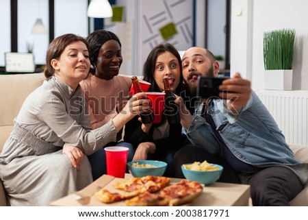 Diverrse group of coworkers taking selfie on smartphone after work at office party. Cheerful colleagues having fun at celebration meting with pizza chips bottles and cups of beer alcohol