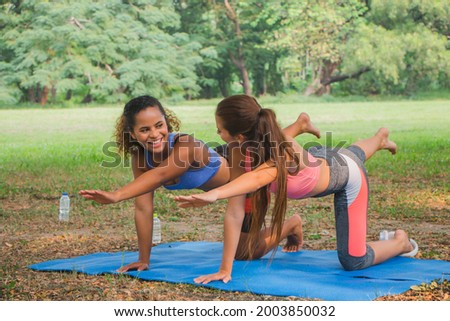 Fitness women practising yoga at a park. Women doing fitness workout in a park.