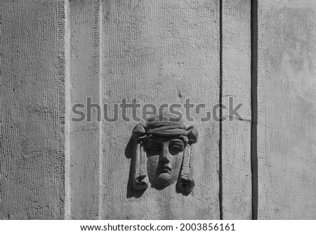 Stucco decoration on the textured facade of an old beige house in the form of a woman's head in a biblical headdress with deep shadows. A detail of classical architecture-mascaron-for creative design. Royalty-Free Stock Photo #2003856161