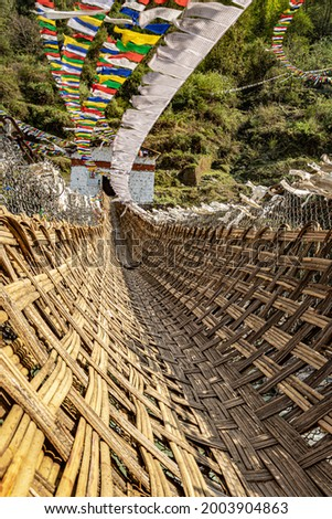 ancient holy bamboo bridge with many buddhist holy flags from unique perspective image is taken at chaksam bridge tawang arunachal pradesh india.