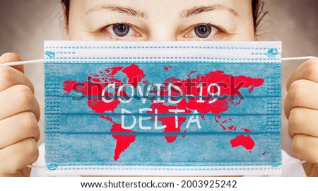 Face mask in hand with world map and inscription COVID 19 DELTA . Delta variant outbreak around the world