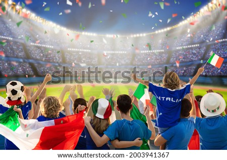 Italy football supporter on stadium. Italian fans on soccer pitch watching team play. Group of supporters with flag and national jersey cheering for Italia. Championship game. Forza Azzurri Royalty-Free Stock Photo #2003941367