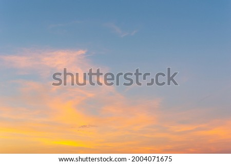 Beautiful Vivid sky painted by the sun leaving bright golden shades.Dense clouds in twilight sky in winter evening.Evening Vivid  sky with clouds. Royalty-Free Stock Photo #2004071675
