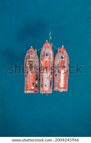 Three fishing boats together with shallow coral reef below, drone aerial ariel uav view orange boat blue water color contrast no people and copy space