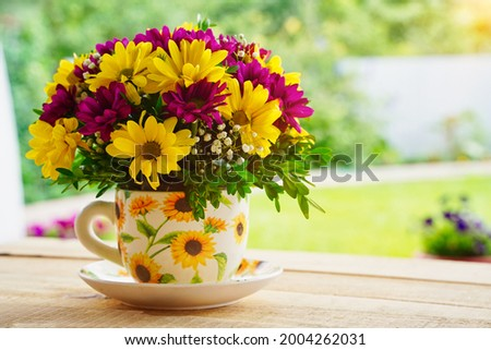 Composition of flowers in a tea mug on a wooden table in the morning in summer or spring. Postcard good morning, Happy Mother's Day, March 8th.