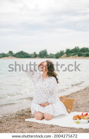 Young beautiful pregnant woman in a beautiful dress near the sea. Picnic. Summer.