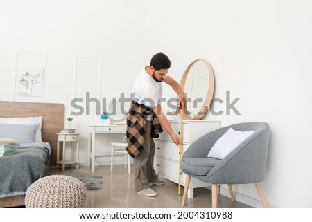 Male carpenter using tape measure in room Royalty-Free Stock Photo #2004310988