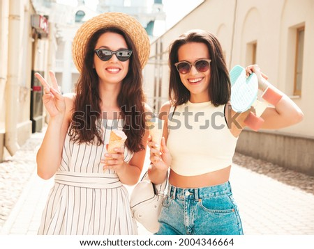 Two young beautiful smiling hipster female in trendy summer clothes and dress.Sexy carefree women posing on the street background. Positive models eating tasty ice cream in waffles cone at sunset Royalty-Free Stock Photo #2004346664