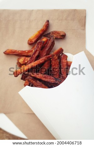 Carrot fries in a cardboard box. Vegetarian fast food dish. Grilled vegetables. BBQ cooking concept for people who do not eat
