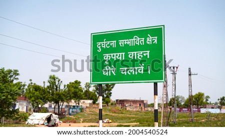 Warning sign board with written Hindi Language. Road sign board to aware people to go slowly in populated area.