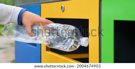 Bin. Child hand throwing plastic bottle recycling container garbage sorting rubbish collection bin. Close up hand put bottle plastic trash can. Child trash recycle bin. Kid recycle plastic garbage can Royalty-Free Stock Photo #2004674903