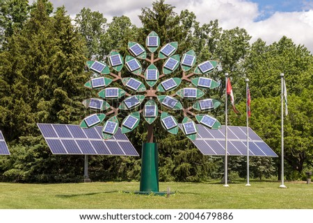 Solar panels on the leaves of a tree shaped metal structure. Three solar panels and flags, including the Canadian flag, in the background.