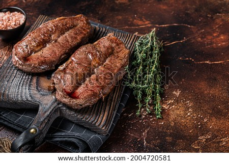 BBQ roasted Shoulder Top Blade cut or Australia wagyu oyster blade beef steak. Dark background. Top View. Copy space Royalty-Free Stock Photo #2004720581