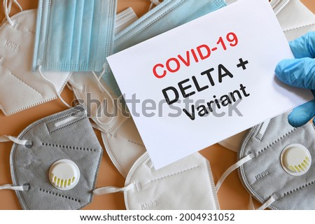Doctor's hand in blue glove with white paper and text Covid-19 Delta + Variant with various protection masks on background. COVID-19 delta variant strain protection concept.