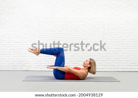 Classic pilates, the hundred drill. Caucasian woman in sportswear lying on her back on a mat and does workout in loft fitness studio indoor, side view Royalty-Free Stock Photo #2004938129